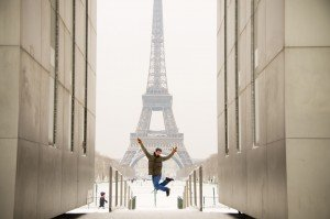 Vacation portrait of man jumping with happiness in front of Eiffel Tower Paris