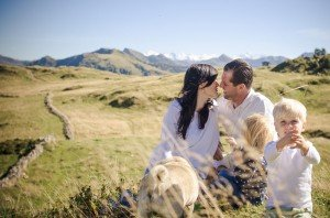 Romantic couple photo kissing with family in Austrian Alps by Anette Gottlicher