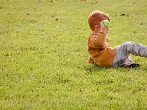 Young boy relaxes on vacation in London park in summer
