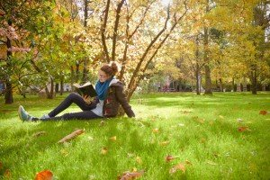 Travelling student reading in sunny garden in Paris France
