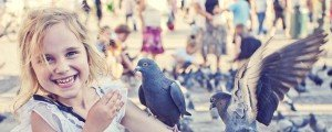 Sample image vacation photo of happy girl with pigeons in Krakow Poland.