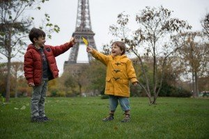 Laughing children with Eiffel Tower tourists on holiday in Paris France