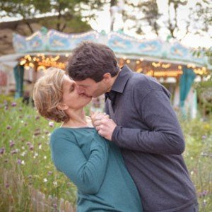 Loving kiss between married husband and wife by Paris carousel in intimate romantic photo session