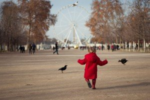 Child in red coat chases birds on vacation in Tuileries Paris France