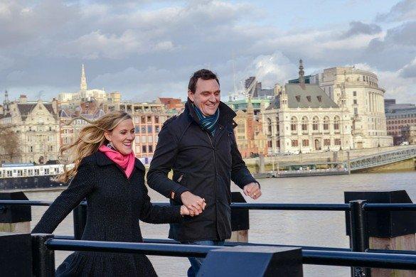 Couple on vacation run along pier in London by TripShooter honeymoon photographer