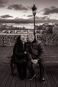 Romantic honeymoon photos of couple kissing on love bridge in Paris France