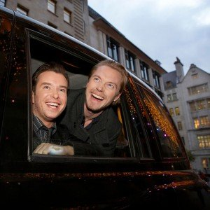 Boyzone portrait laughing in car by David Woolfall photographer in London