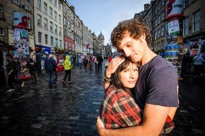 Loving couple embrace in city by Glasgow photographers Chris Logue and Ewan Cameron