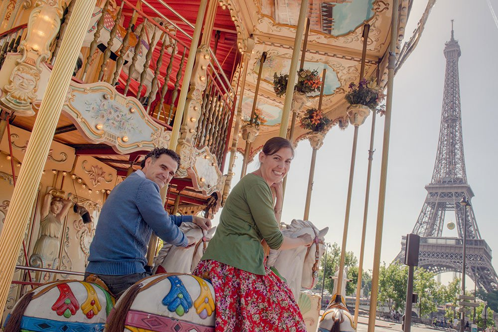 Happy couple on carousel on Paris honeymoon