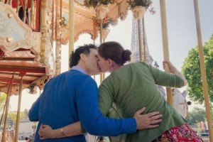 Romantic photo of honeymoon couple kissing on carousel at Eiffel Tower