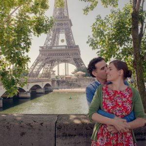 Honeymoon couple kissing by the Seine and Eiffel Tower in Paris