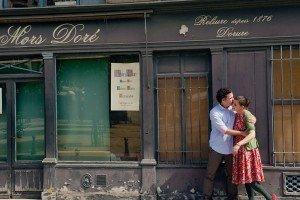 Honeymoon couple kissing outside Paris cafe