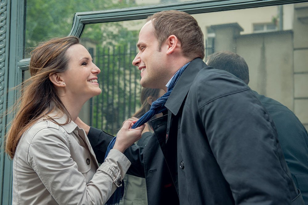 Cute couple portrait of woman holding boyfriend's tie by Paris photographer Jade Maitre for TripShooter
