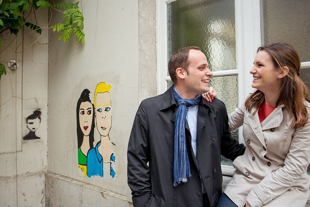 Smiling couple in love with graffiti in Les Marais, by Paris photographer Jade Maitre for TripShooter