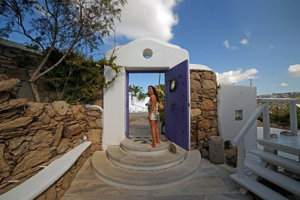 Woman standing by a typical Greek blue