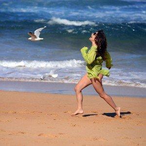Woman and bird racing on the beach in Greece