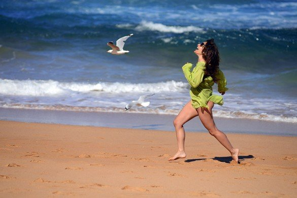 Woman and bird racing on the beach in Greece