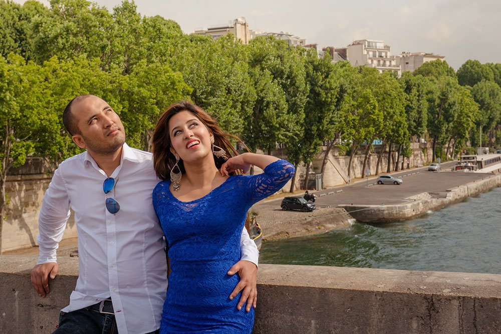 A loving honeymoon couple by the Seine on a romantic photo shoot in Paris France