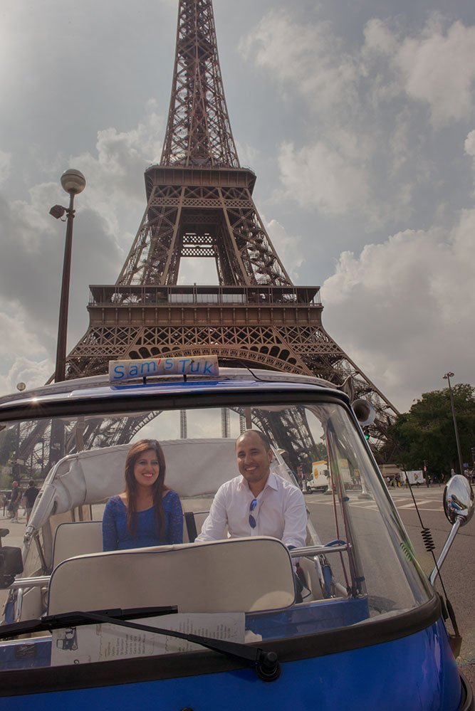 A loving honeymoon couple share a French tuk tuk on a romantic photo shoot in Paris France