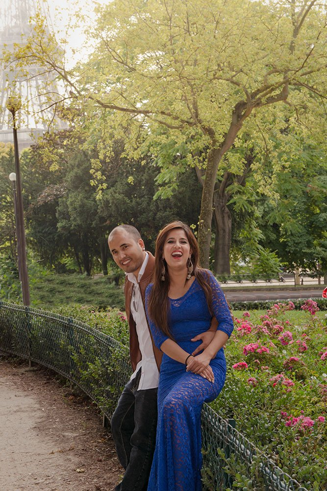 A happy couple on honeymoon laugh in French gardens on a romantic photo shoot in Paris France