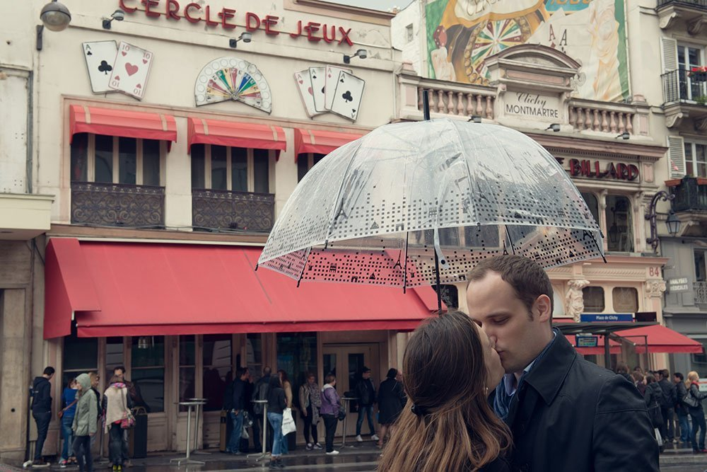 Couple kissing under umbrella at Clignancourt by Paris photographer Jade Maitre for TripShooter