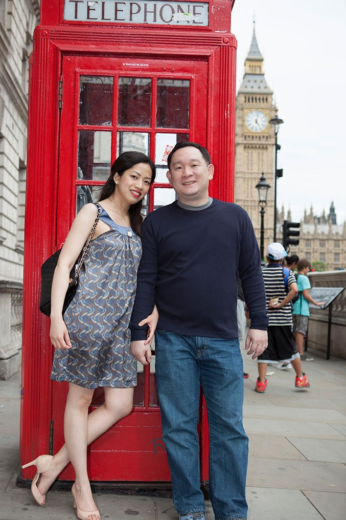 Smiling couple by a red telephone box, by London photographer David Woolfall for TripShooter