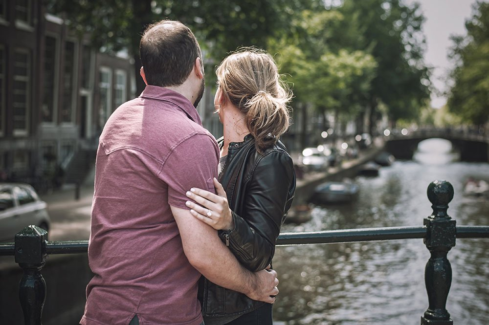 Couple embrace at Amsterdam canals in portrait by TripShooter Amsterdam photographer Sal Marston