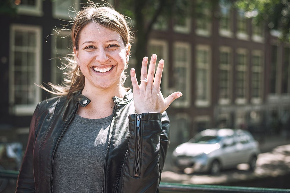 Happy engaged fiancee shows engagement ring in Amsterdam