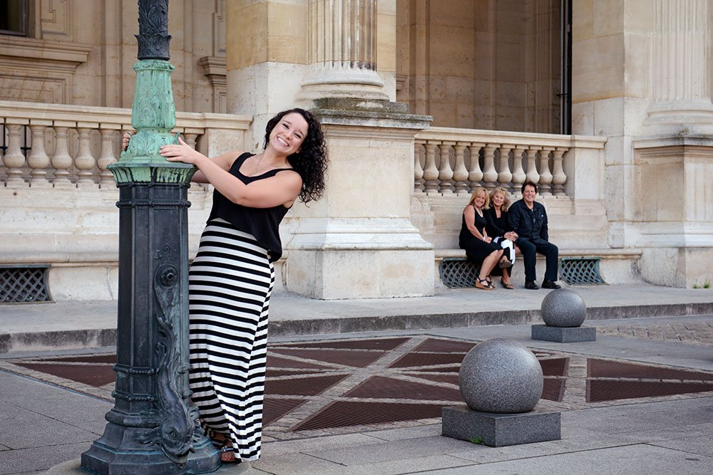 Smiling grand-daughter and family at birthday celebration at Louvre by Paris photographer Jade Maitre for TripShooter