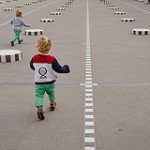 Photo of children running at Palais Royale comlumns by Paris photographer Jade Maitre