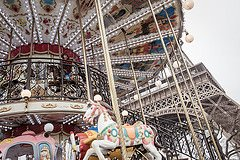 Photo of boy on carousel with Eiffel Tower by Paris photographer Jade Maitre