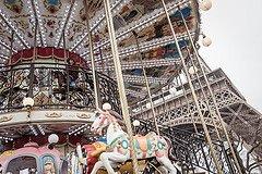 Photo of boy on carousel with Eiffel Tower by Paris photographer Jade Maitre