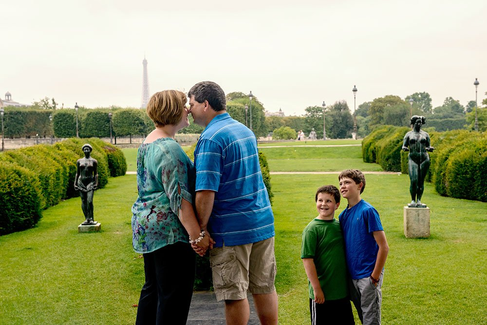 Parents kissing at Tuileries Gardens in Paris by TripShooter Paris photographer Pierre