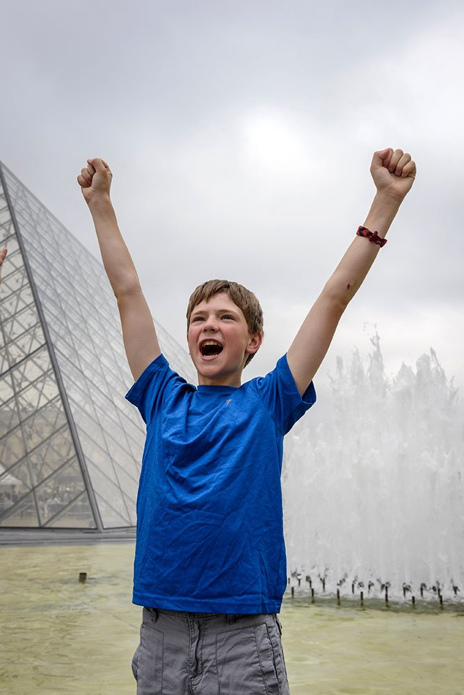 Happy excited boy on Paris vacation at Louvre, by TripShooter Paris photographer Pierre