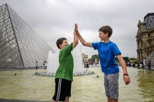Kids high five on Paris vacation at Louvre by TripShooter Paris photographer Pierre