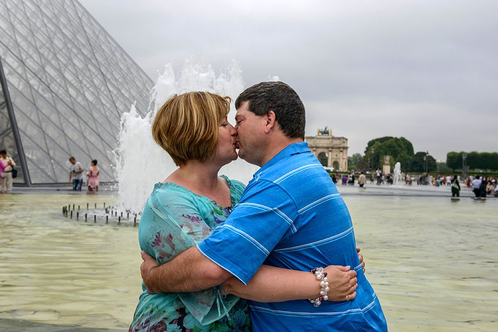 Couple kissing at Louvre by TripShooter Paris photographer Pierre