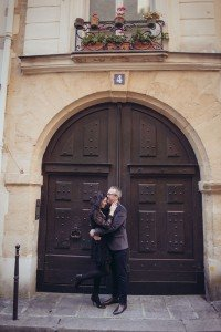 Loving couple photos in Paris in front of historic door in Le Marais, by TripShooter photographer in Paris Jade Maitre