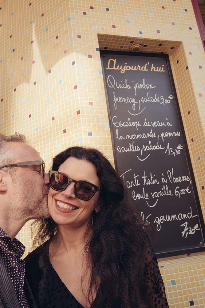 Fun couple photos in Paris on Le Marais with cafe menu, on photo tour by TripShooter Paris photographer Jade Maitre