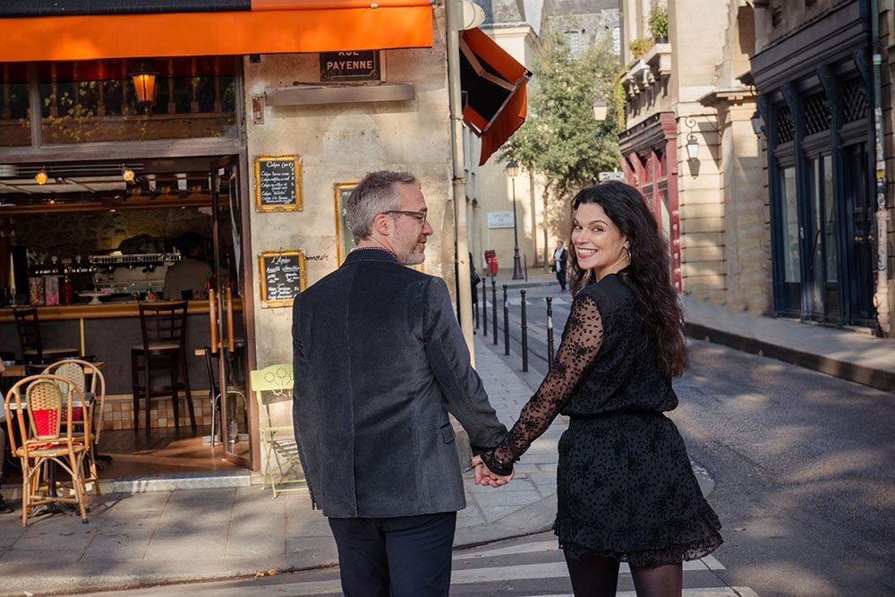 Couple cross Paris street on Marais photo tour, by Paris photographer Jade Maitre