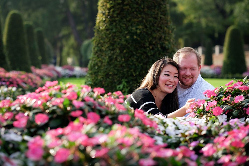 Couple smiling in park with flowers, Romantic Madrid photoshoot by TripShooter Madrid Photographer Ludovic Magnoux