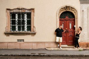 Travelers in Hungary play in front of red door, by TripShooter Budapest photographer Melinda Guerini Temesi