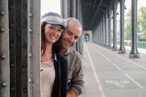 Couple peek behind bridge at Bir Hakeim, photos by TripShooter's Paris photographer Pierre Turyan