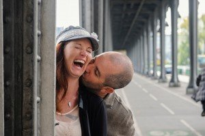 Woman laughs as partner kisses her in Paris, by TripShooter's Paris photographer Pierre Turyan