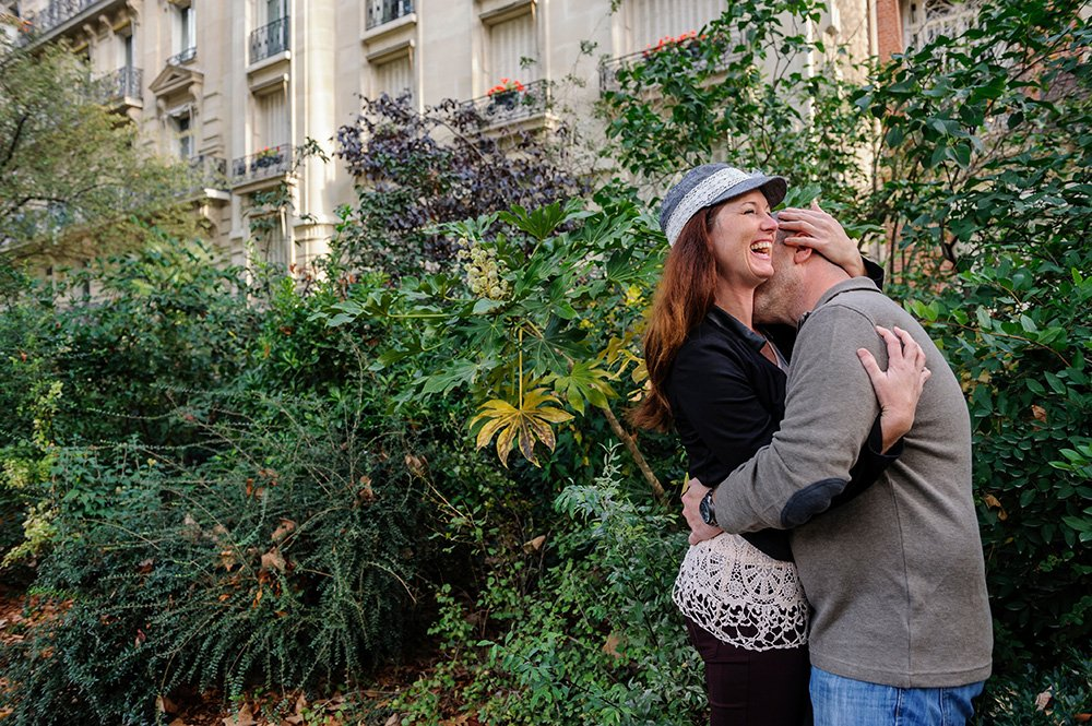 Couple laugh and embrace at Champ de Mars, by TripShooter's photographer in Paris Pierre Turyan