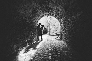 Anniversary in Italy couple embrace under sunlit arch, by TripShooter's photographer in Italy Giancarlo Malandra