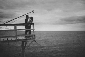 Couple embrace on pier by TripShooter photographer in Italy Giancarlo Malandra
