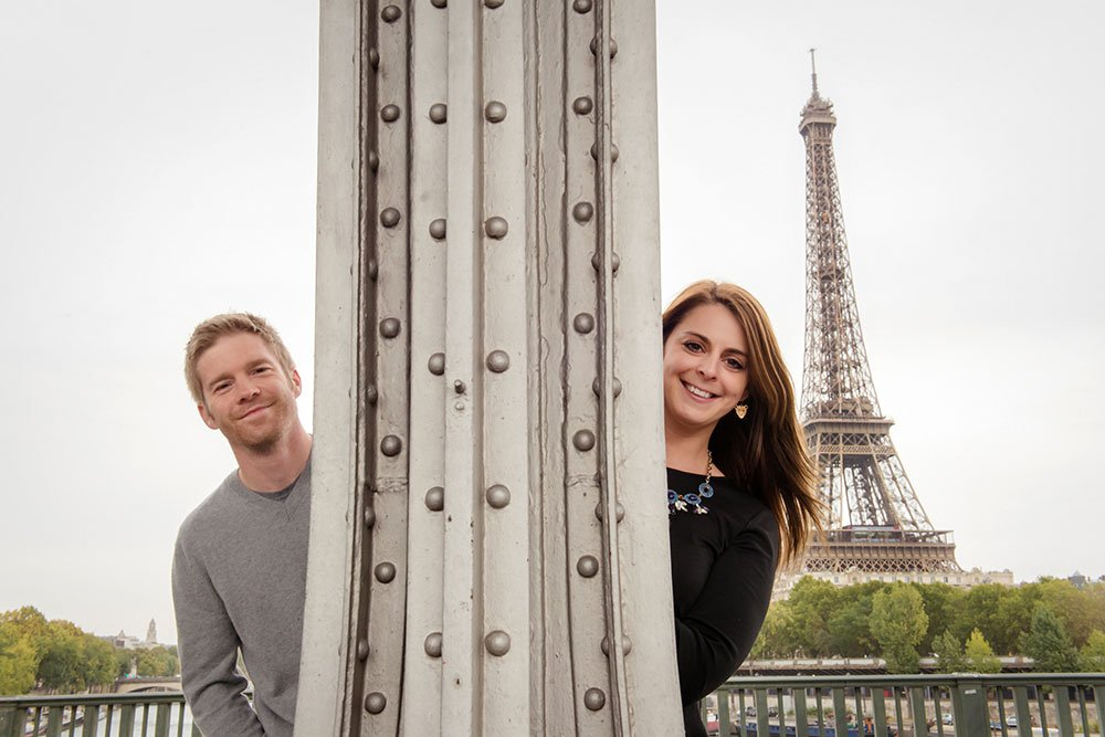Cute couple photo with Eiffel Tower. Photo Loving couple stroll in Paris. Portrait by TripShooter Paris photographer Jade Maitre