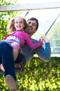 Father and daughter play on swing, by TripShooter Zurich photographer Cloudia Chen