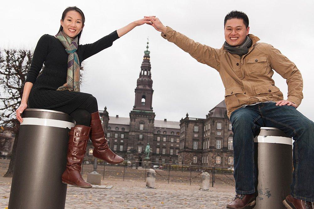 Fun couple photo in Copenhagen of couple linking hands above Town Hall, photo by TripShooter's Copenhagen photographer Matthew Harrison