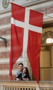 Loving couple smile beneath Denmark flag, photo by TripShooter's Copenhagen photographer Matthew Harrison